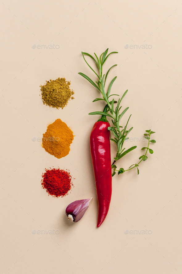 Chili pepper, spicy herbs and spices on a light peach background - Stock Photo - Images