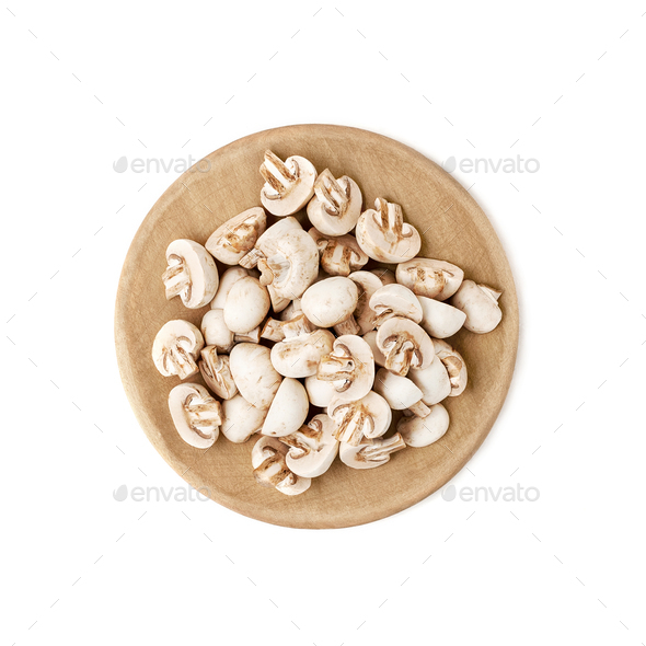 Cut mini champignons on a round wooden cutting board. Isolated o - Stock Photo - Images