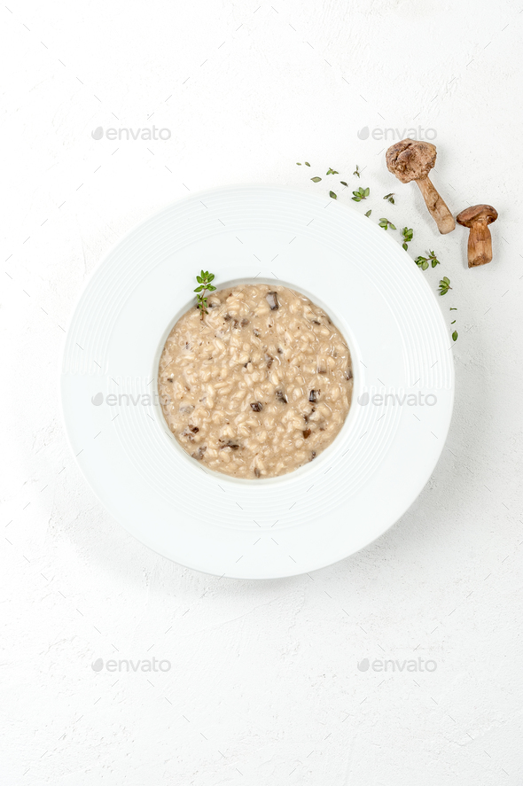 Risotto with porcini mushrooms in a white plate on a white table - Stock Photo - Images