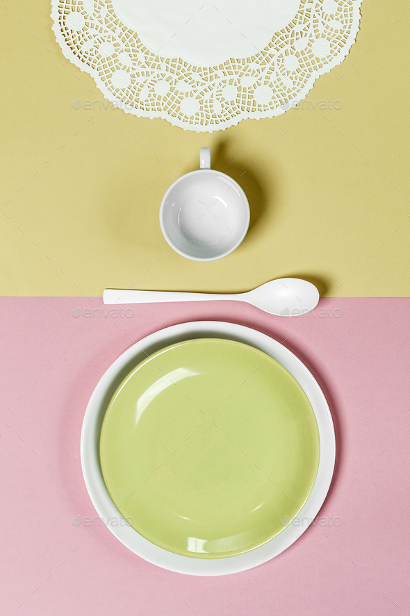 Table setting on a light pink-green background: light green plat - Stock Photo - Images