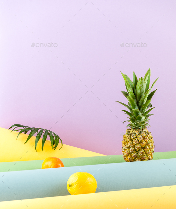Pineapple, lemon and mandarin on a combined colored background. - Stock Photo - Images
