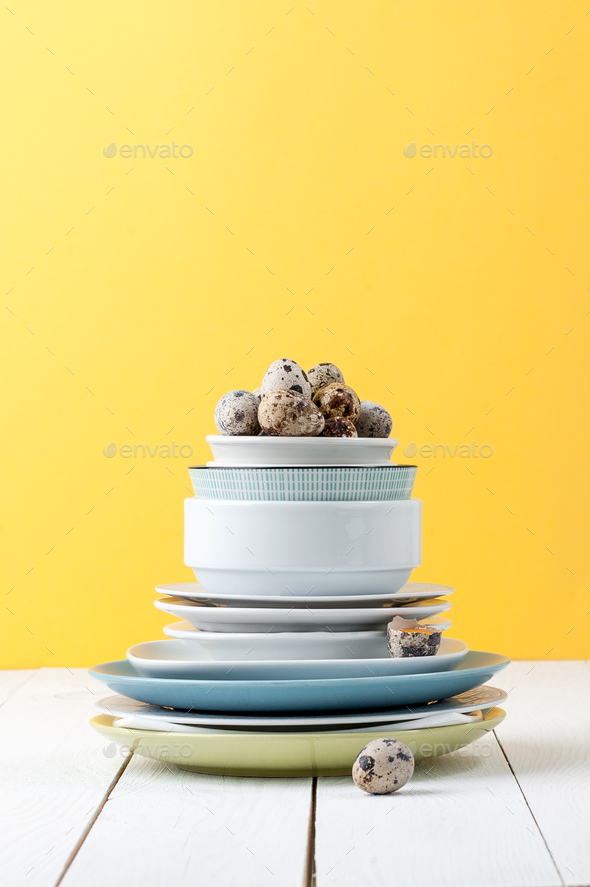 A stack of different tableware and quail eggs on a white wooden - Stock Photo - Images