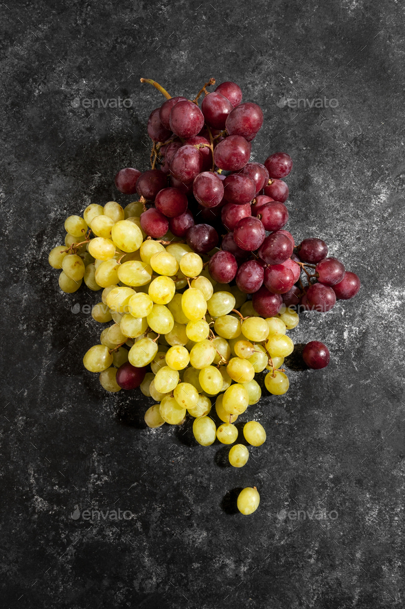 White and red bunch of grapes on a black worn background. - Stock Photo - Images