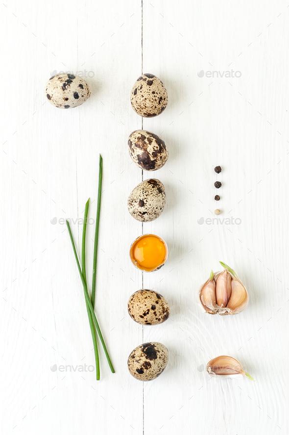 Minimalistic still life with quail eggs, garlic and shiny onion - Stock Photo - Images
