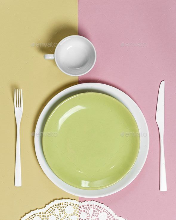 Light green plate and white cutlery on a pink-green background. - Stock Photo - Images