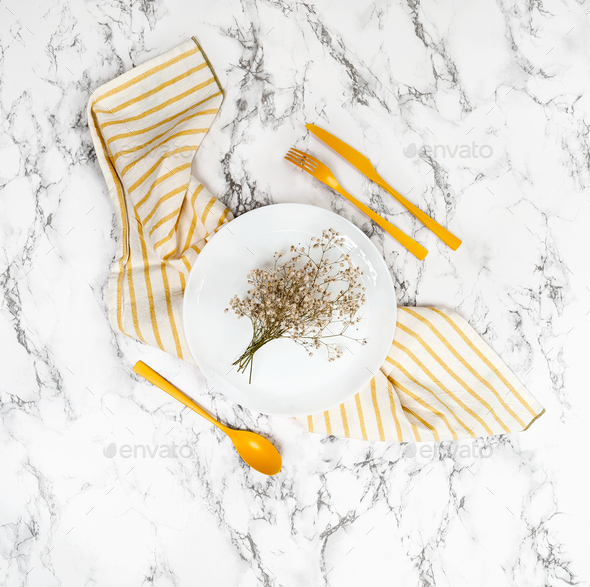 White plate and yellow cutlery on the marble table. - Stock Photo - Images
