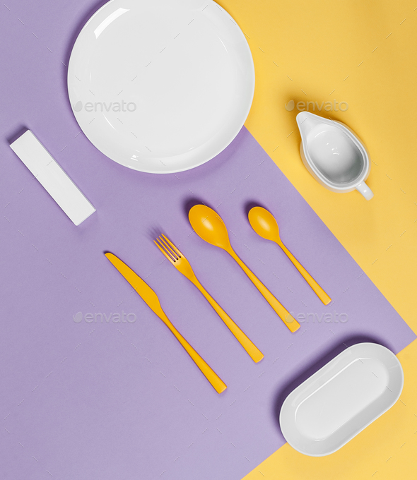White tableware and yellow cutlery on a yellow-violet pastel bac - Stock Photo - Images