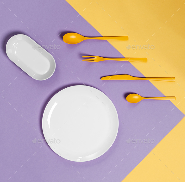 White plate and yellow cutlery on a pastel yellow-lilac backgrou - Stock Photo - Images