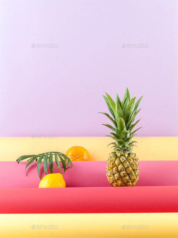 Pineapple, lemon and mandarin on a combined colored background w - Stock Photo - Images