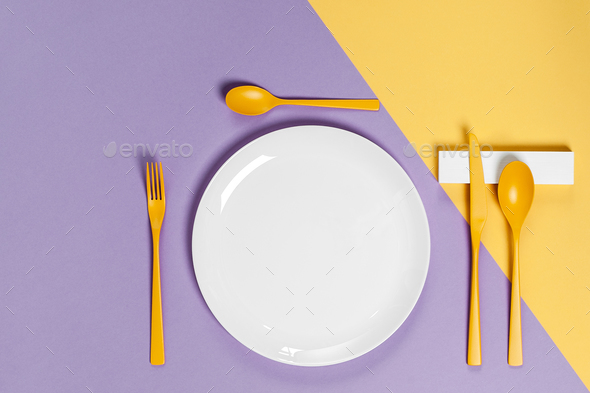 White utensils and yellow cutlery on a pastel colored background - Stock Photo - Images