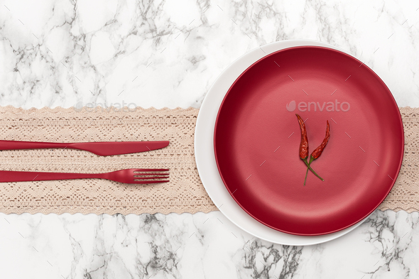 A red plate, cutlery and two chili peppers on a marble table. - Stock Photo - Images