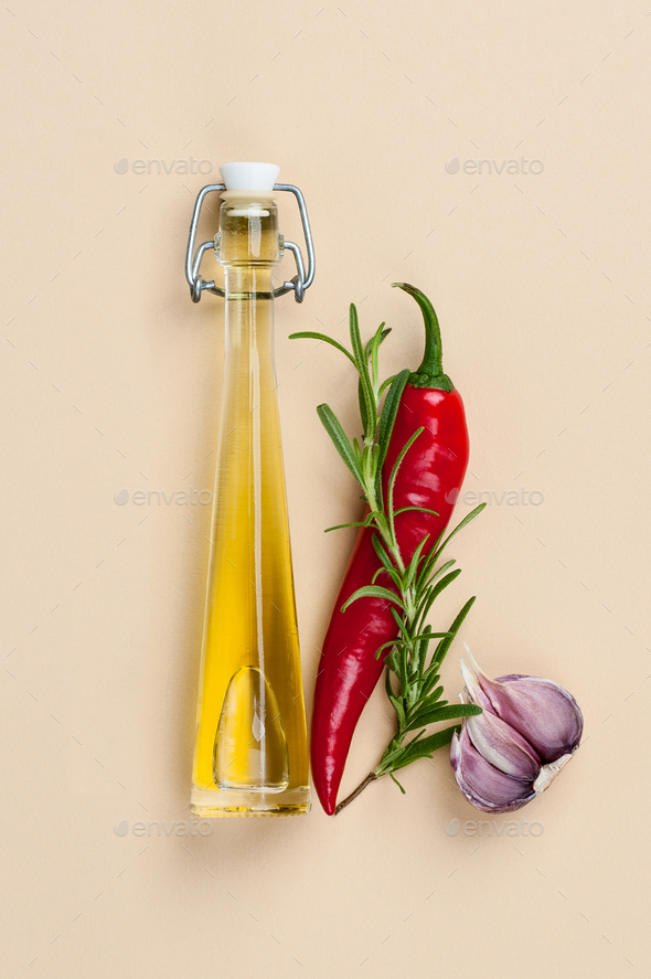 Olive oil, chili pepper, rosemary and garlic on a light beige ba - Stock Photo - Images