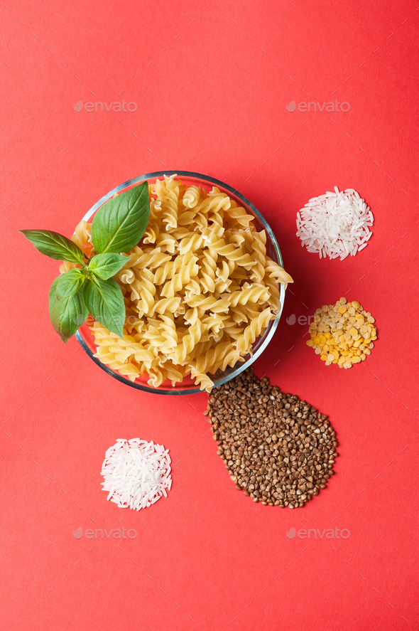 Pasta, rice, buckwheat and lentils on a red background. - Stock Photo - Images