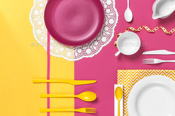 Colorful dishes on a yellow rose table. Stylish arrangement. - Stock Photo - Images