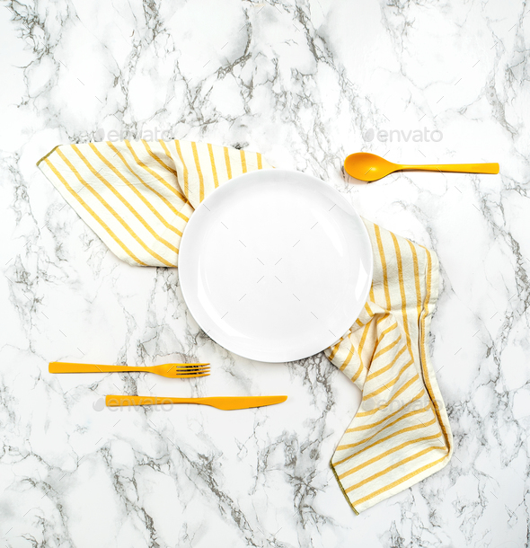 White dish, striped napkin and yellow cutlery on the marble tabl - Stock Photo - Images