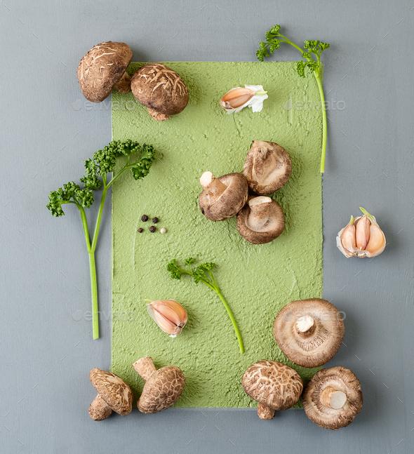 Fresh shiitake mushrooms, parsley and garlic on an abstract gray - Stock Photo - Images