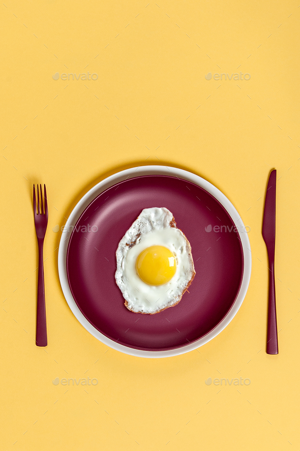 Scrambled eggs on a maroon dish with burgundy cutlery on a light - Stock Photo - Images