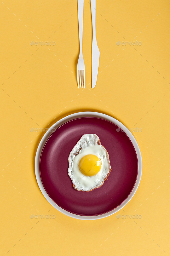 Fried egg on a burgundy plate on a yellow background. Breakfast - Stock Photo - Images