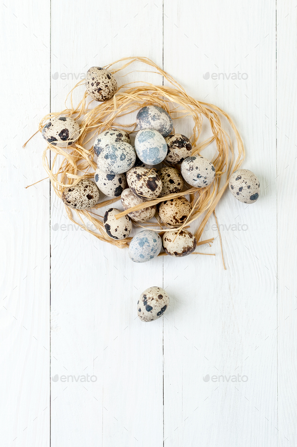 Fresh quail eggs in a nest of hay in a white wooden table. - Stock Photo - Images