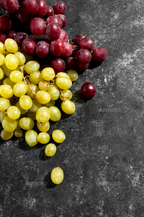 White and red grapes on a black aged background. - Stock Photo - Images