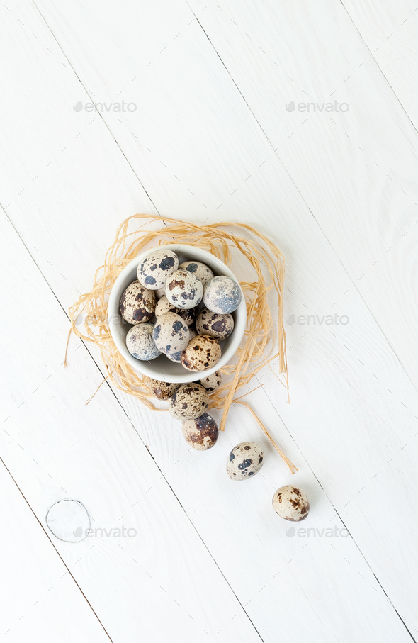 Fresh quail eggs in a white bowl on a wooden table. Flat-lay. - Stock Photo - Images