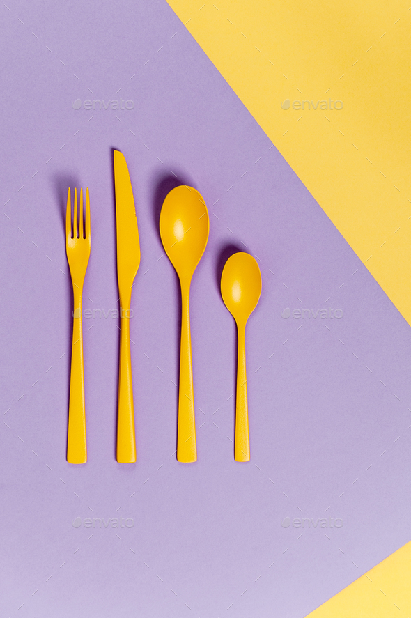 Yellow cutlery on a pastel yellow-lilac background. Colors in th - Stock Photo - Images