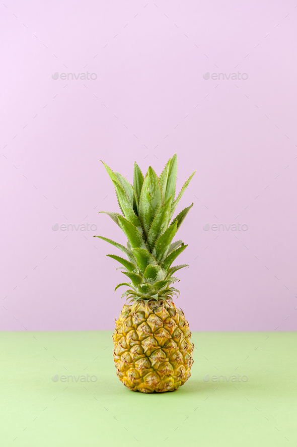 Mini pineapple on a light lilac-green background. - Stock Photo - Images
