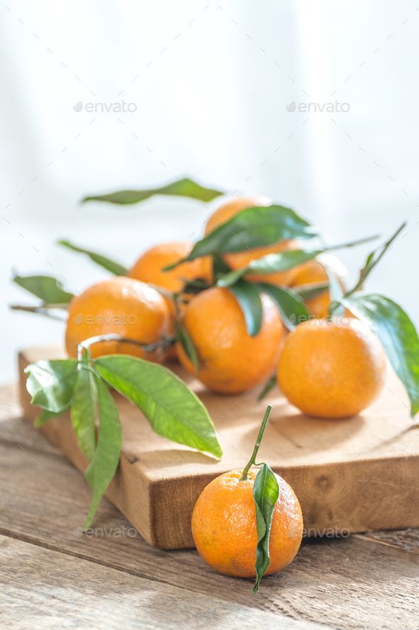 Ripe mandarins with twigs on an old wooden table. - Stock Photo - Images