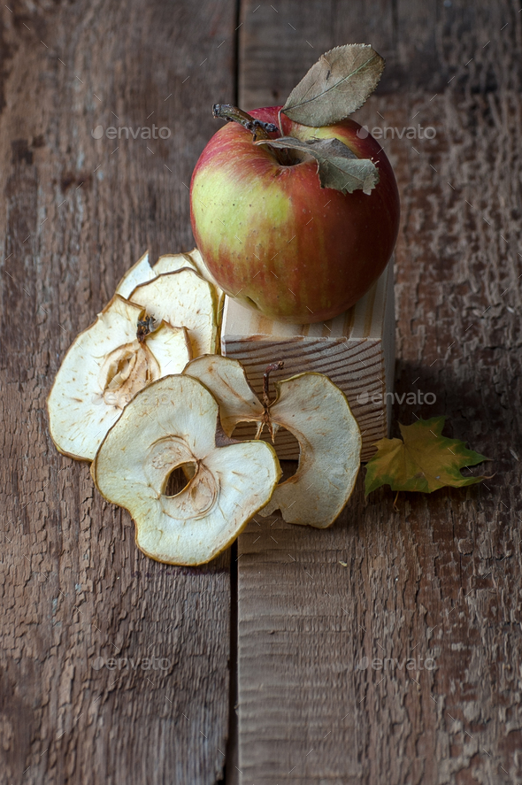 Apple and apple chips on an old wooden table. - Stock Photo - Images