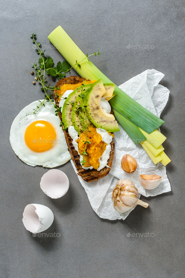 Sandwich with avocado, sweet pepper paste and fried eggs on a gr - Stock Photo - Images
