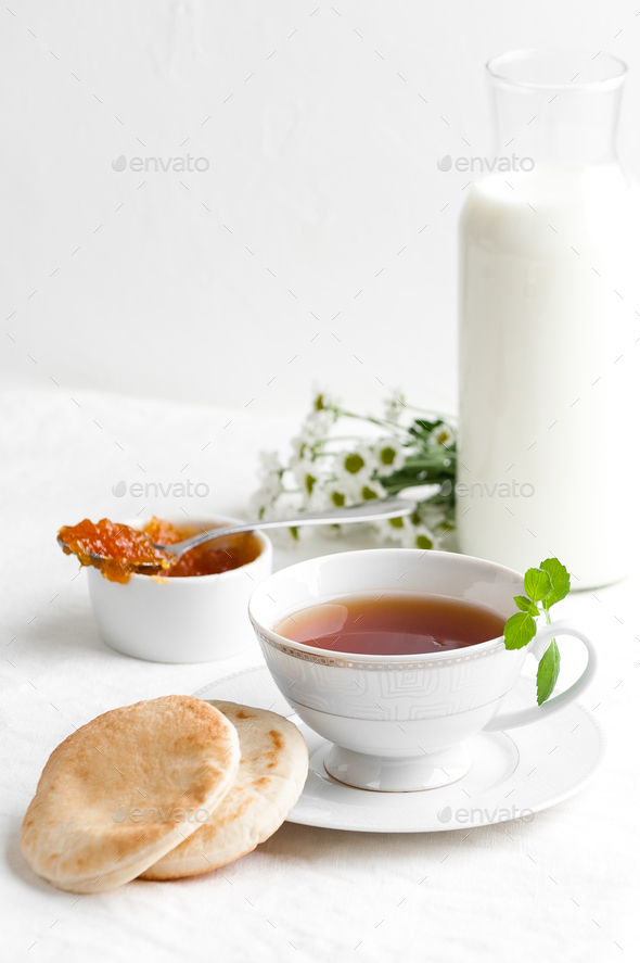 A cup of black tea, jam and a bottle of milk. - Stock Photo - Images