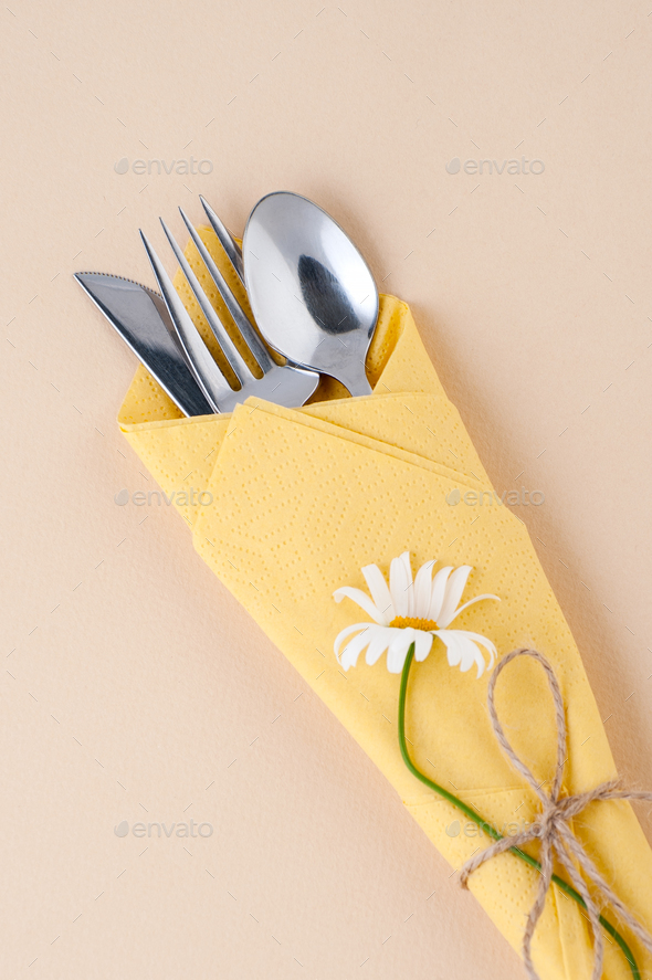 Cutlery wrapped in a yellow napkin on a light peach background. - Stock Photo - Images
