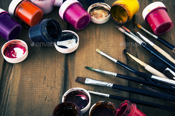 Multicolored acrylic paints and art brushes on a wooden table. - Stock Photo - Images