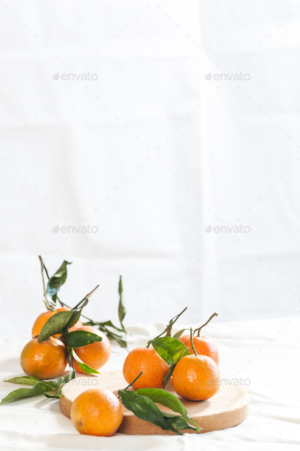 Ripe mandarins with twigs on a round board. A photo with negativ - Stock Photo - Images