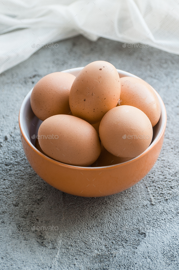 Brown chicken eggs in a bowl on a gray stone table. - Stock Photo - Images
