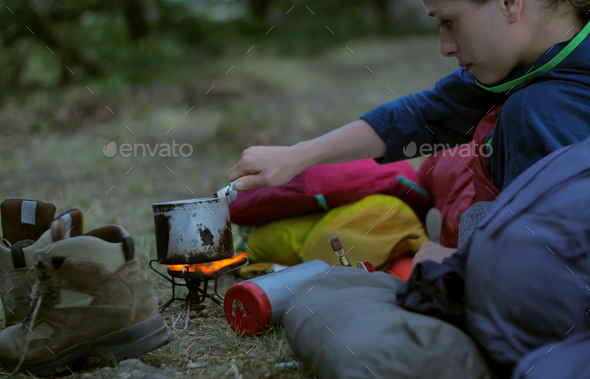 female hiker cooking outdoors - Stock Photo - Images