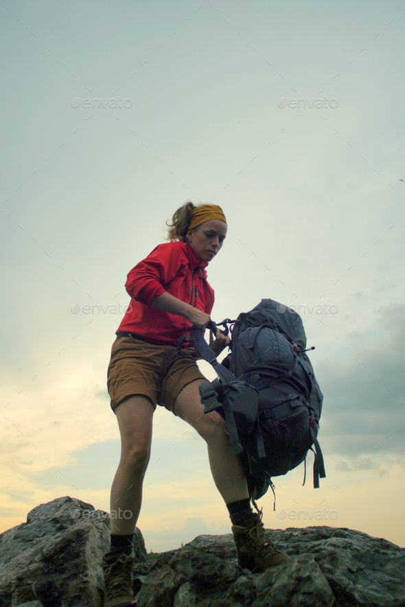 hiker putting on a backpack - Stock Photo - Images