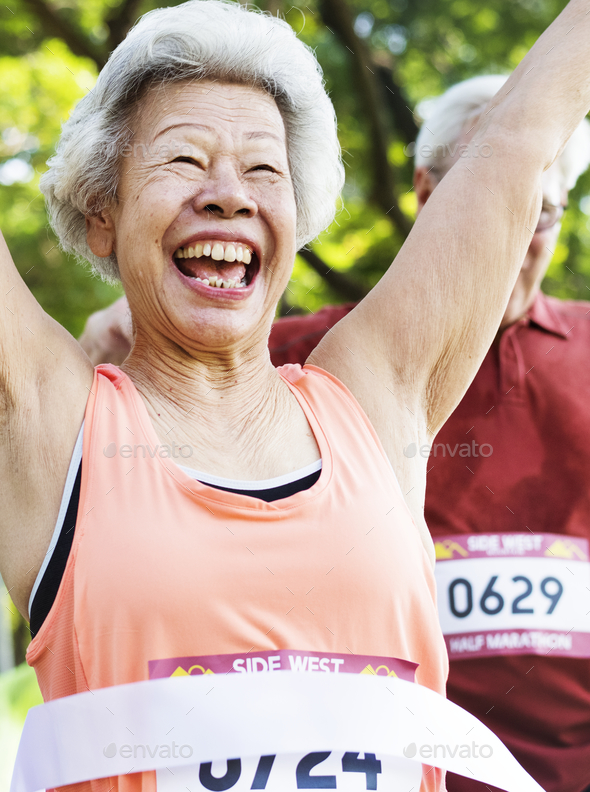Elderly asian woman reaching the finish line - Stock Photo - Images