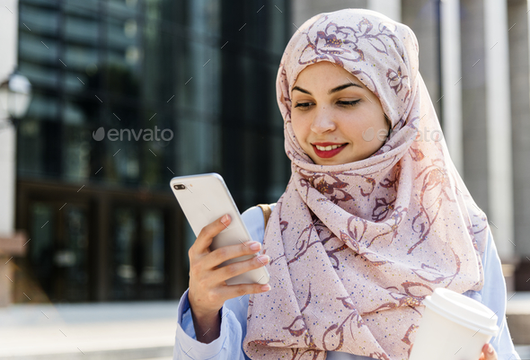 Islamic woman using mobile phone and holding coffee cup - Stock Photo - Images
