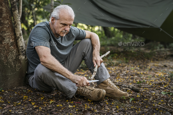 Mature man cutting some firewood - Stock Photo - Images