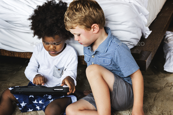 Friends playing with tablet in bedroom - Stock Photo - Images