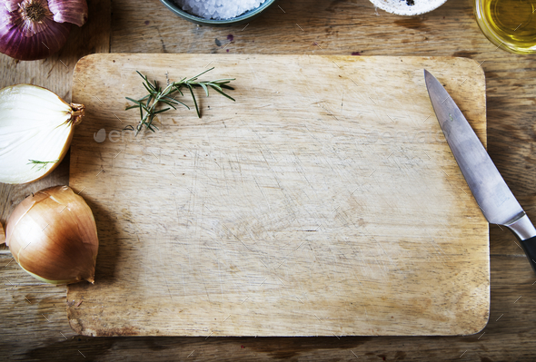 Cutting board and vegetables on a wooden table - Stock Photo - Images