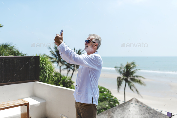 Senior man on vacation taking a selfie - Stock Photo - Images