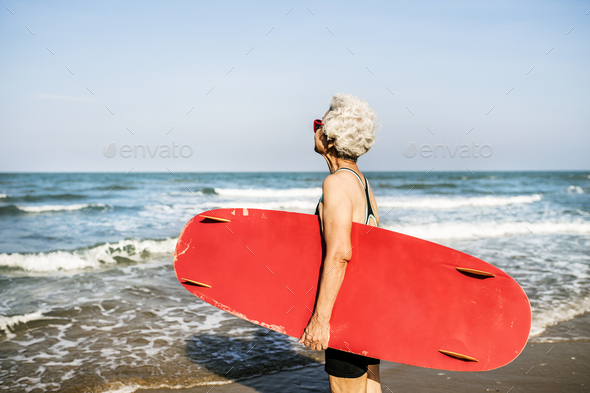 Senior woman holding a surfboard - Stock Photo - Images
