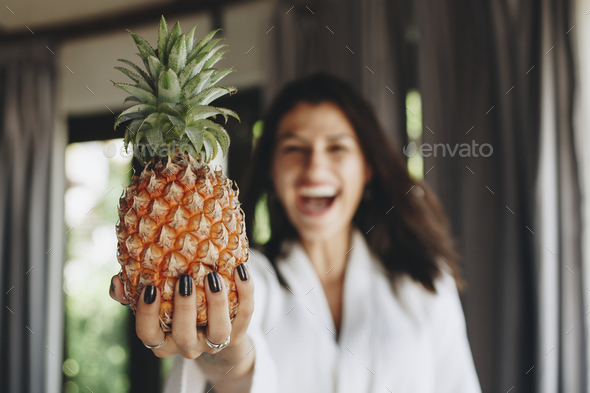 Woman in a bathrobe holding a pineapple - Stock Photo - Images