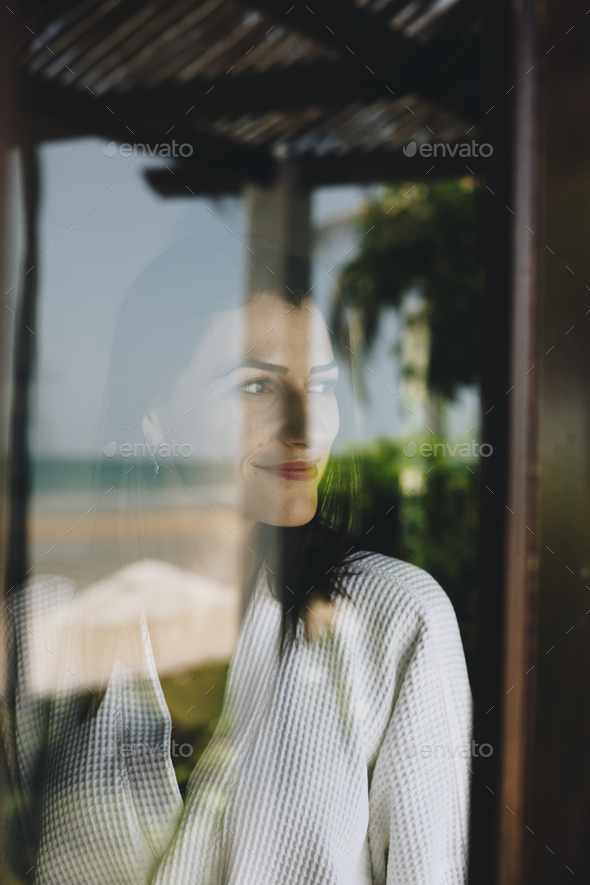 Woman looking out her hotel room window - Stock Photo - Images