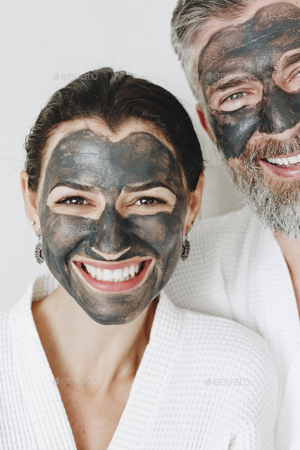 Happy couple wearing a charcoal mask - Stock Photo - Images