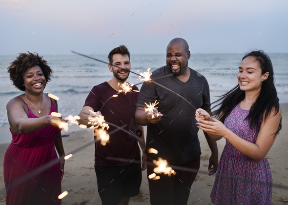 Friends celebrating with sparklers at the beach - Stock Photo - Images