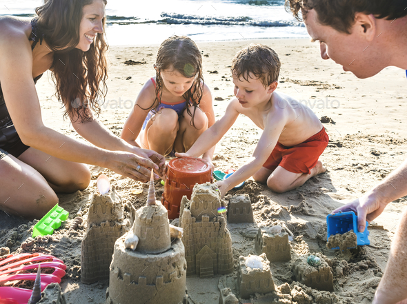 Family playing on the beach - Stock Photo - Images