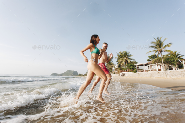 Cheerful couple running at the shore - Stock Photo - Images